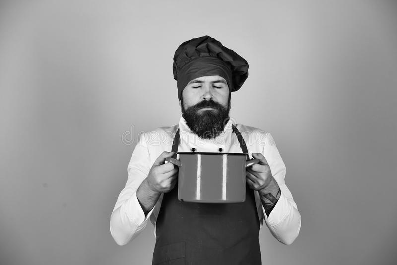 Человек с бородой держит kitchenware на голубой предпосылке стоковые изображения