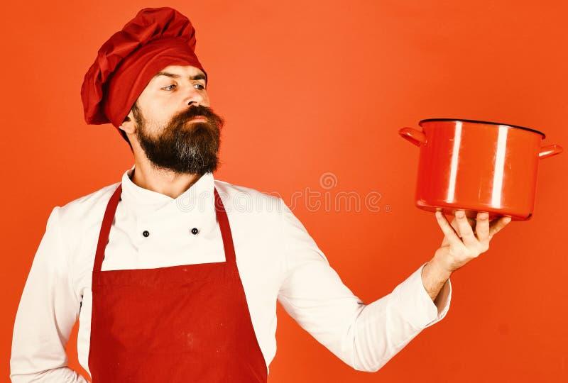 Человек с бородой держит kitchenware на красной предпосылке стоковая фотография