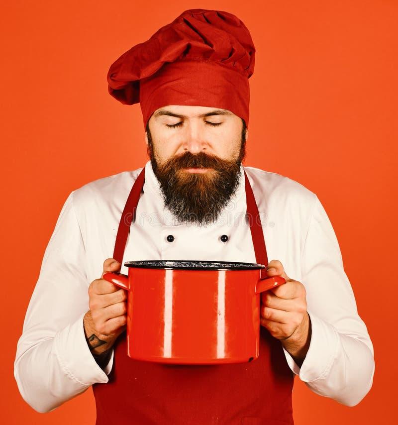 Человек с бородой держит kitchenware на красной предпосылке стоковые фото