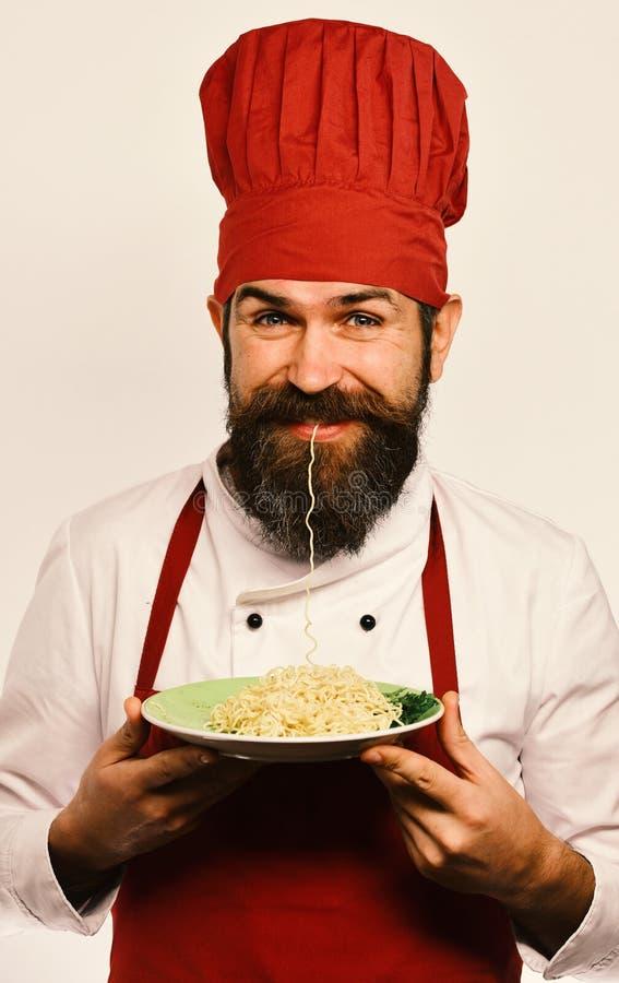 Человек с бородой и лапшой в рте держит вкусное блюдо на белой предпосылке Концепция кухни ресторана Кашевар с счастливым стоковая фотография rf