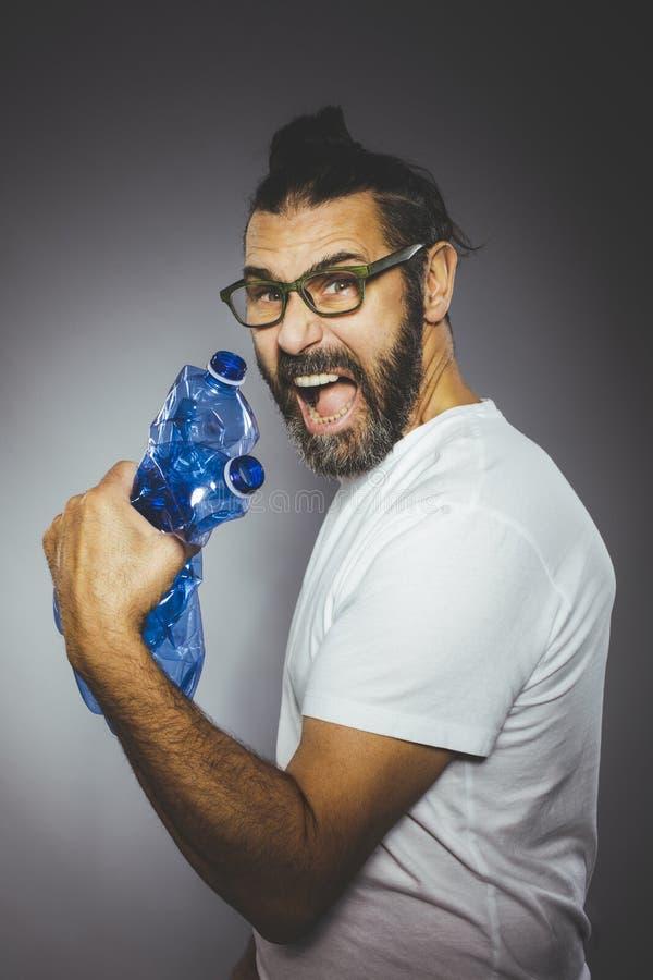 Человек с бородой и очками держит пластиковые бутылки стоковое изображение rf