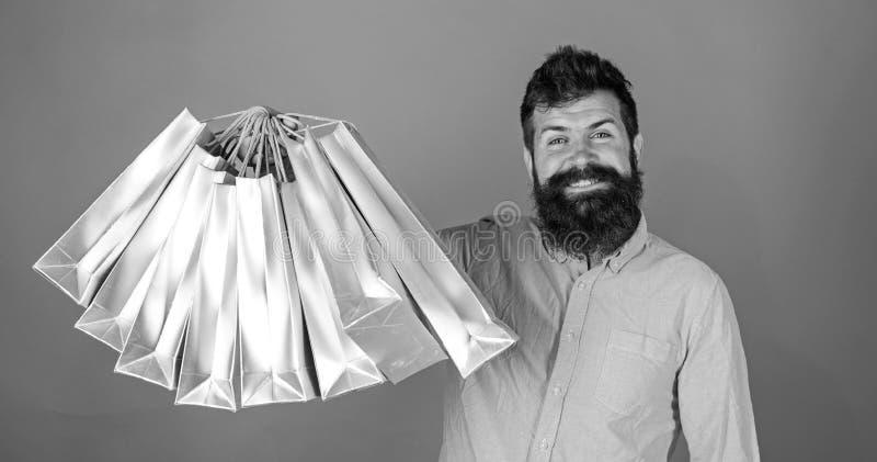 Человек с бородой и усиком держит хозяйственные сумки, красную предпосылку Хипстер на счастливой стороне ходить по магазинам прис стоковая фотография rf