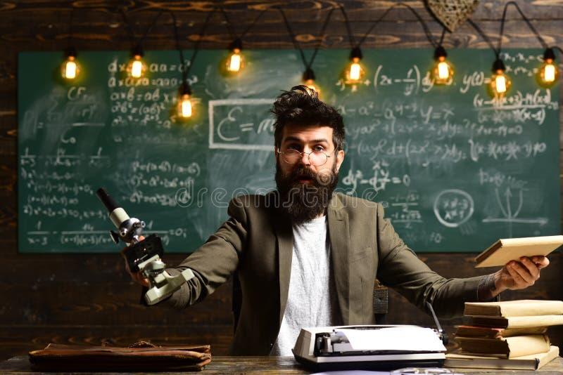 Человек с бородой и усик в университете Бородатый человек с книгой и ретро машинкой Ученый делает исследование с стоковое фото rf