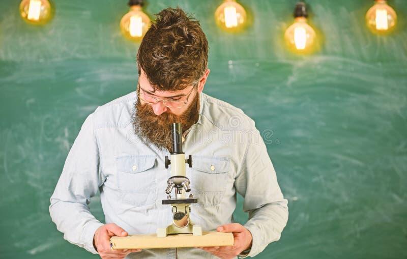 Человек с бородой и усик на занятой стороне Ученый держит книгу и микроскоп, доску на предпосылке r стоковые изображения