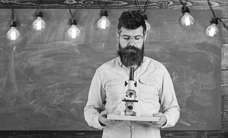 Человек с бородой и усик на занятой стороне Учитель в eyeglasses держит книгу и микроскоп Ученый держит книгу и стоковые фото
