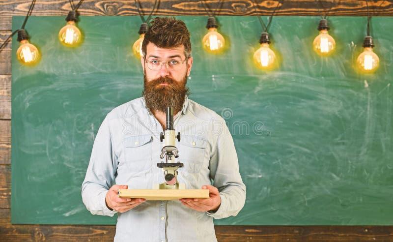 Человек с бородой и усик на спокойной стороне Учитель в eyeglasses держит книгу и микроскоп Ученый держит книгу и стоковые изображения