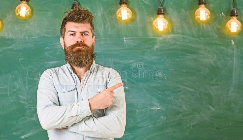 Человек с бородой и усик на строгой стойке стороны перед доской Бородатый хипстер в рубашке, доске дальше стоковая фотография rf