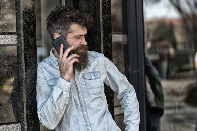 Человек с бородой и усик на строгой стороне говоря, строя на предпосылке Бородатый человек говоря на сотовом телефоне стоковые изображения rf