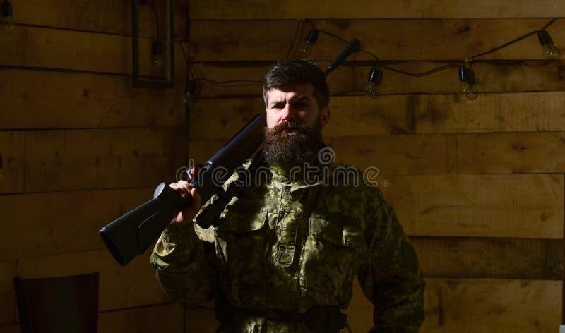 Человек с бородой носит маскировочную одежду, носит винтовку на плече, деревянной внутренней предпосылке Охотник, зверский битник стоковая фотография rf