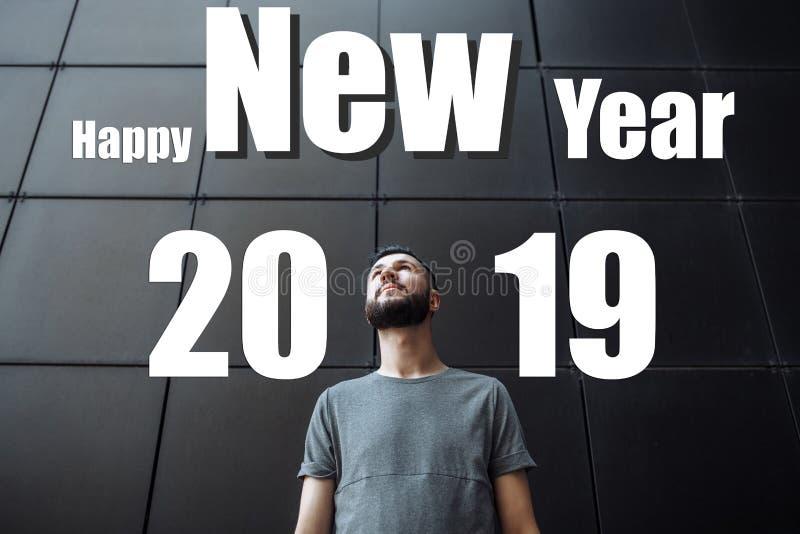 Человек с бородой, парень смотрит вверх, против черной предпосылки Отправьте SMS С Новым Годом! 2019 Принципиальная схема рождест стоковое изображение rf