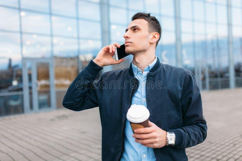 Человек с бумажным стаканчиком кофе, идет через город, красивый парня в стильных одеждах, на телефоне стоковые фотографии rf