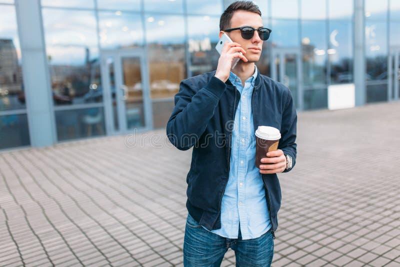 Человек с бумажным стаканчиком кофе, идет через город, красивый парня в стильных одеждах и солнечные очки, звоня телефонный звоно стоковая фотография rf