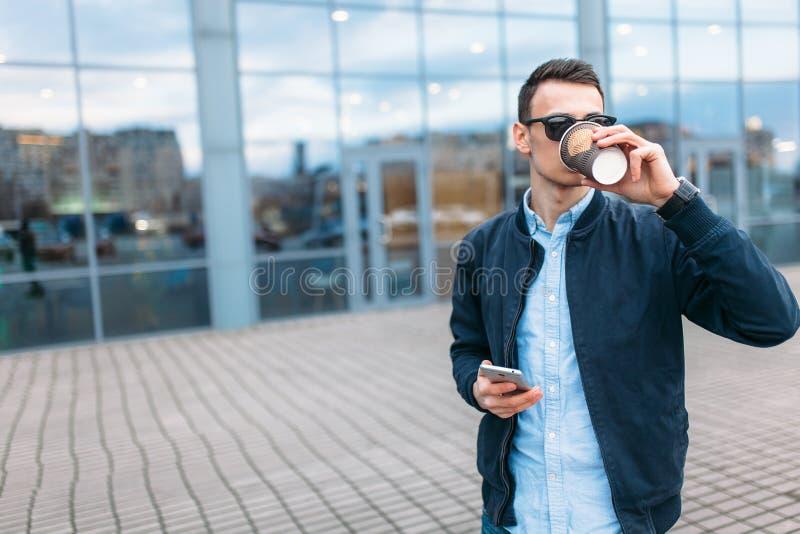 Человек с бумажным стаканчиком кофе, идет через город, красивый парня в стильных одеждах и солнечные очки, звоня телефонный звоно стоковые фото
