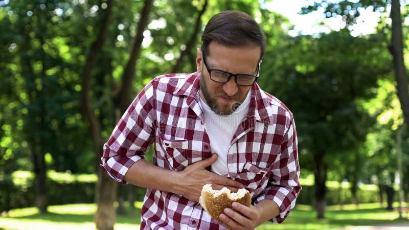 Человек с бургером в тошноте чувства руки, пищевом отравлении высококалорийной вредной пищи, опьянении тела стоковое изображение rf