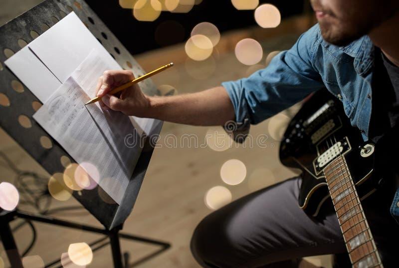 Человек с гитарой писать к книге музыки на студии стоковые фото