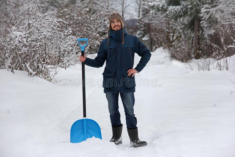 Человек с голубым лопаткоулавливателем снега стоковые изображения