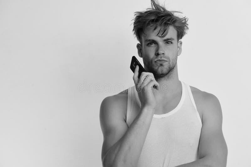 Человек с грязными волосами держит мобильный телефон Технология и современная концепция образа жизни Человек держит устройство стоковое изображение