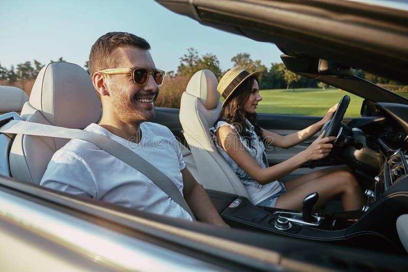 Человек с девушкой управляя cabriolet стоковое фото