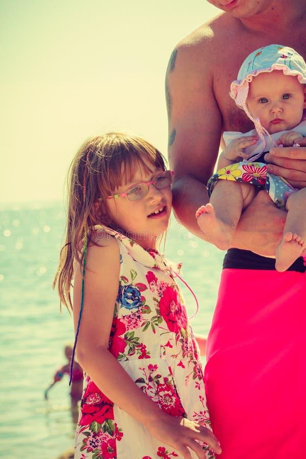 Человек с 2 детьми представляя на побережье стоковое фото