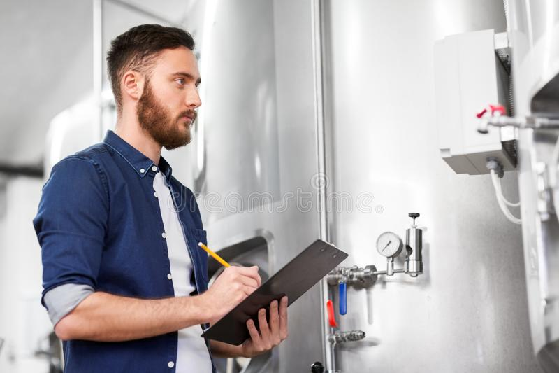 Человек с доской сзажимом для бумаги на винзаводе ремесла или заводе пива стоковое изображение rf