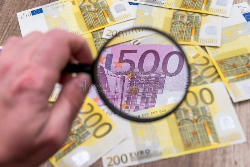 Человек с евро находки лупы стоковая фотография