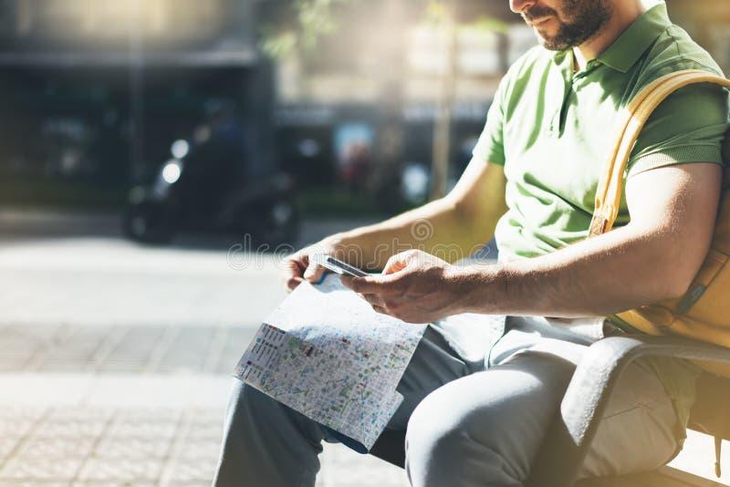 Человек с желтым смартфоном удерживания рюкзака, туристским смотря городом карты на такси предпосылки, маршруте планирования хипс стоковое фото