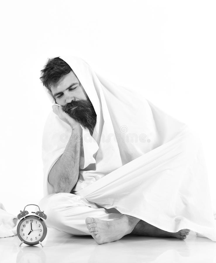 Человек с затишьем, пробуренная сторона сидит под одеялом около будильника Человек хочет остаться в кровати, белой предпосылке стоковые фото
