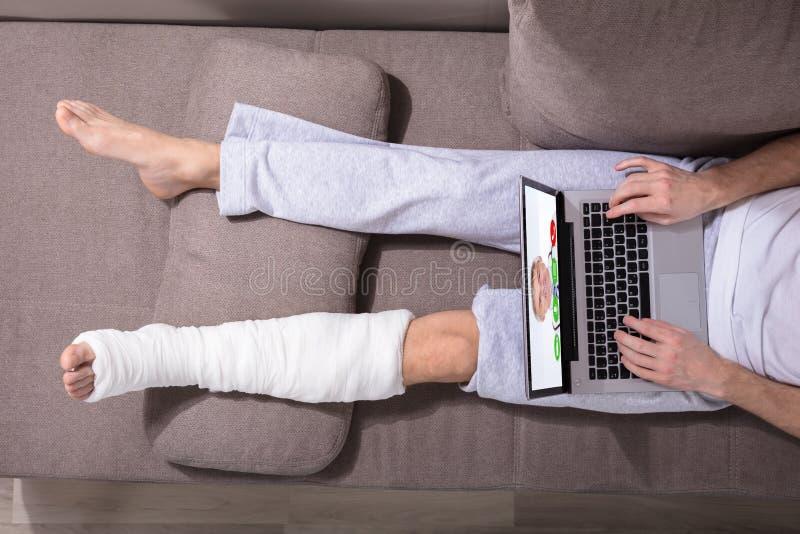 Человек с заштукатуренной ногой используя компьтер-книжку стоковое изображение rf
