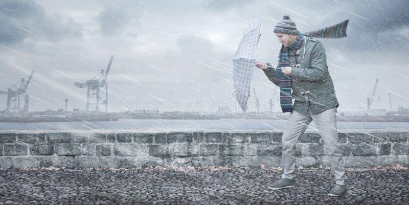 Человек с зонтиком смотрит на сильный ветер и дождь стоковое изображение rf