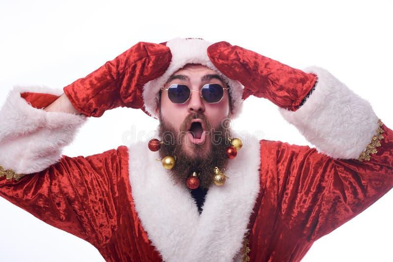 человек с игрушками рождества в бороде и в костюме Санта Клауса держит руки около его головы стоковое фото rf
