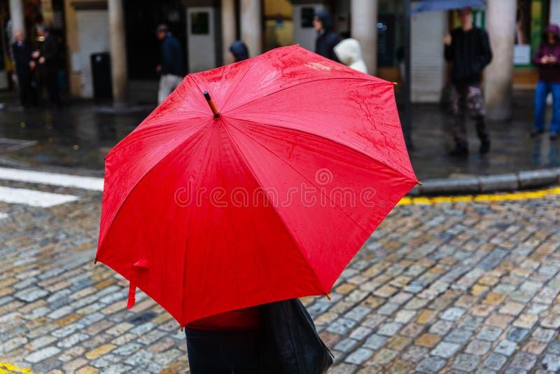 Человек с красным зонтиком дождя пересекает улицу города стоковое изображение