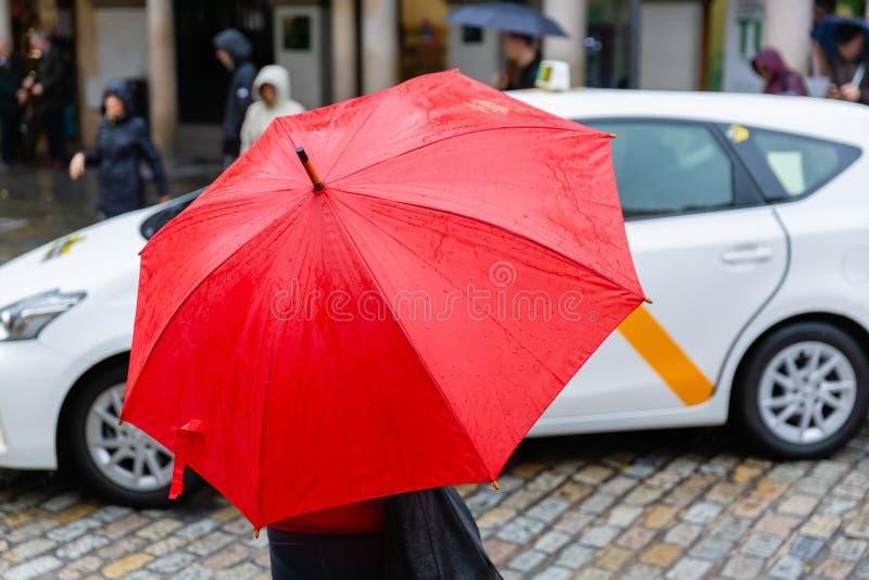 Человек с красным зонтиком дождя пересекает улицу города стоковые изображения rf