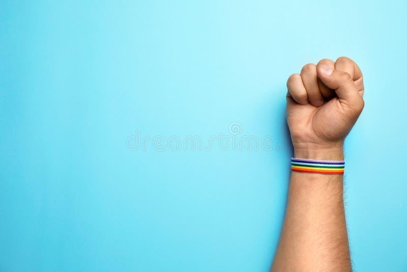 Человек с лентой радуги на голубой предпосылке, космосе для текста Символ гея стоковое изображение