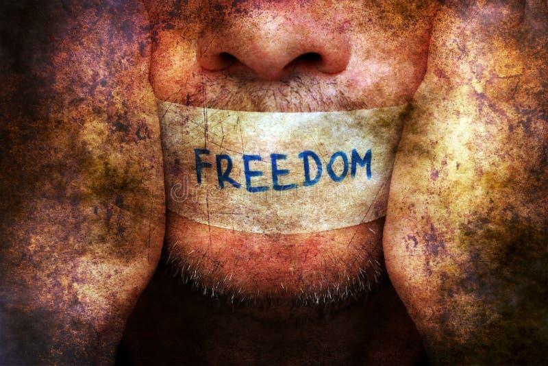 Человек с лентой свободы над ртом стоковое фото