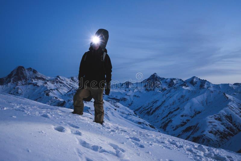 Человек с лыжей headlamp и рюкзака нося носит положение перед изумительным горным видом зимы Подъем путешественника на ноче на стоковая фотография rf
