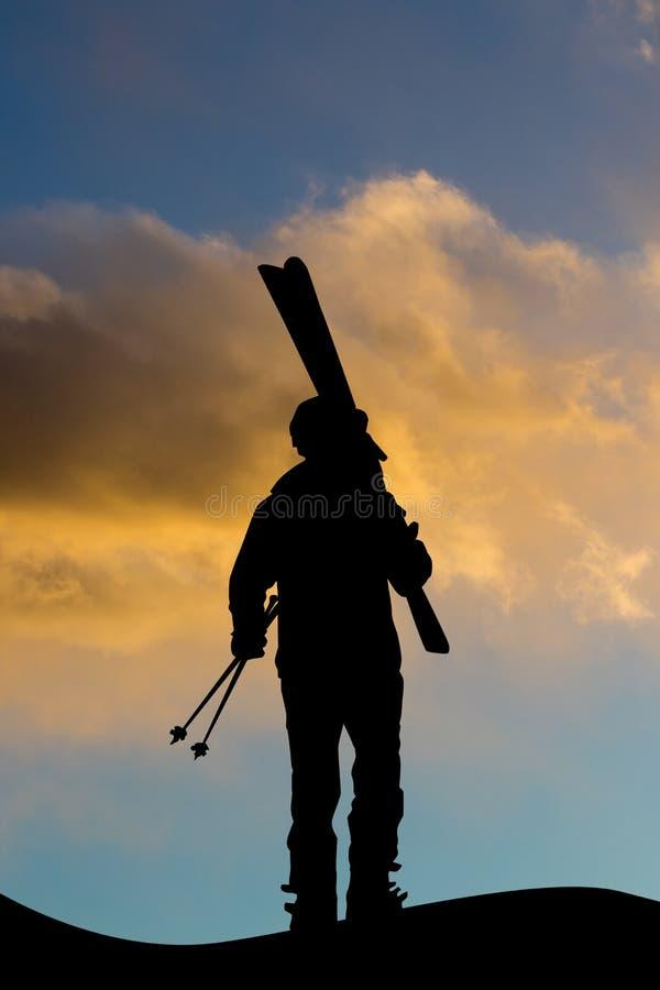 Человек с лыжным оборудованием на заходе солнца стоковая фотография rf