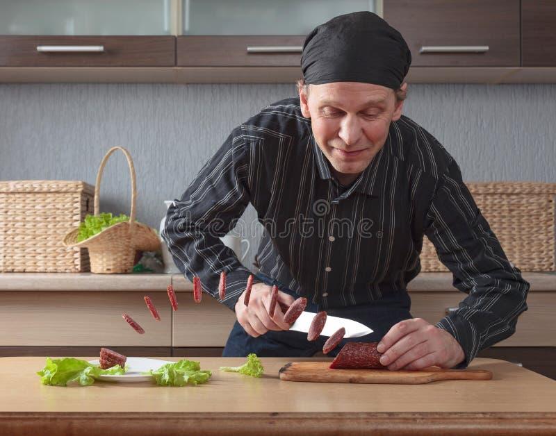 Человек с ножом режет сосиску частей стоковая фотография rf