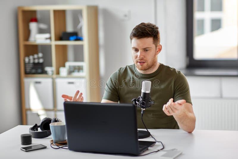 Человек с офисом ноутбука и микрофона дома стоковое изображение rf