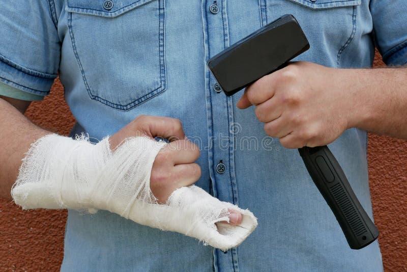 Человек с перевязанной рукой и молотком стоковая фотография rf
