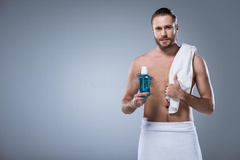 человек с полотенцем ванны на плече держа бутылку с rinse зуба в руке, стоковые фотографии rf
