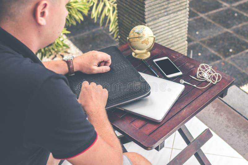 Человек с роскошным случаем компьтер-книжки питона snakeskin на таблице вне азиатского сада Концепция моды людей Сумка компьтер-к стоковые изображения