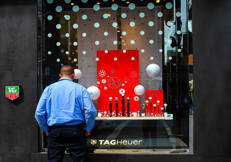 Человек с руками в карманн и назад к камере смотря в окне магазина на вахтах TAGHeuer стоковые изображения rf