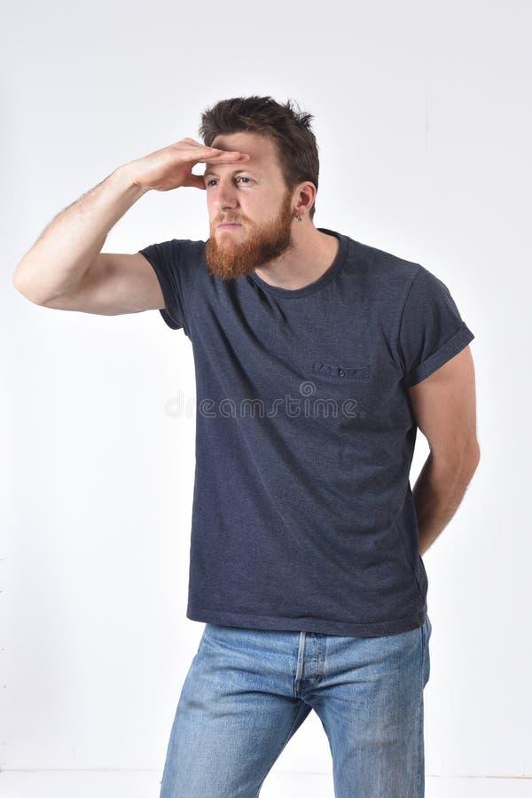 Человек с рукой во фронте смотря прочь на белой предпосылке стоковые фото