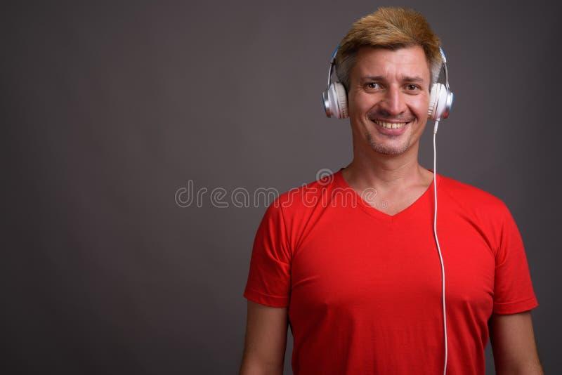 Человек с светлыми волосами слушая к музыке против серой предпосылки стоковое изображение