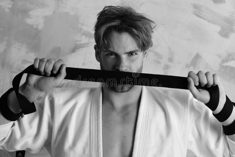 Человек с серьезным визированием и щетинка на красочной предпосылке Гай представляет в белом кимоно держа черный пояс Боец карате стоковое фото rf