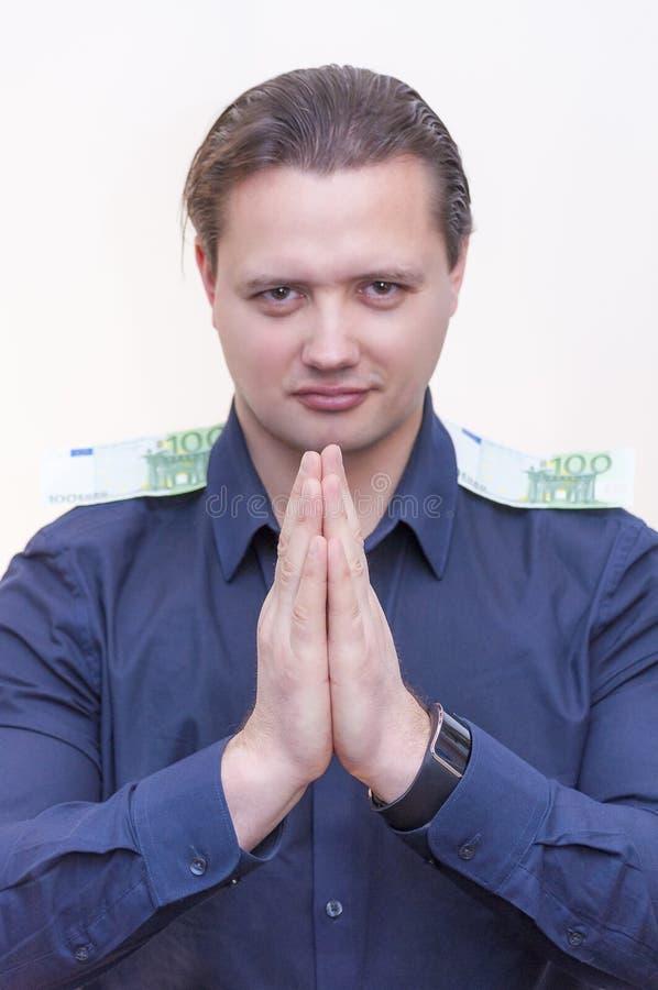 Человек с сжиманными руками и 100 банкнотами евро на его плечах стоковая фотография