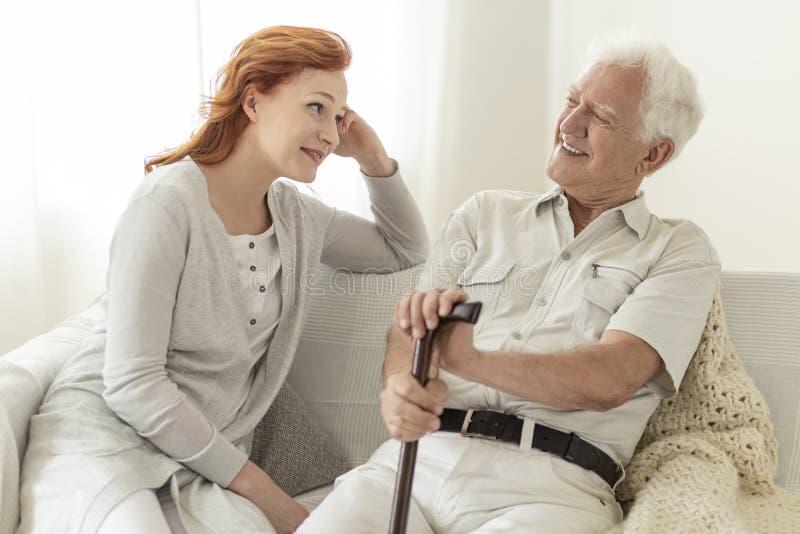 Человек с тросточкой говоря к его дочери и усмехаться стоковые изображения