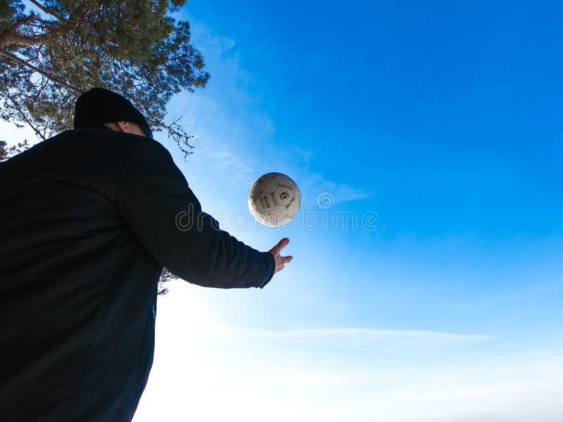 Человек с футбольным мячом в конце-вверх зимы стоковые изображения
