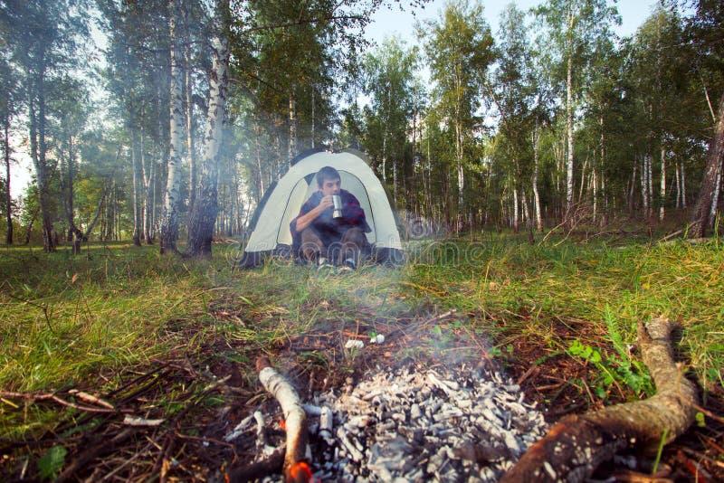 человек с чашкой около лагерного костера в шатре стоковое фото