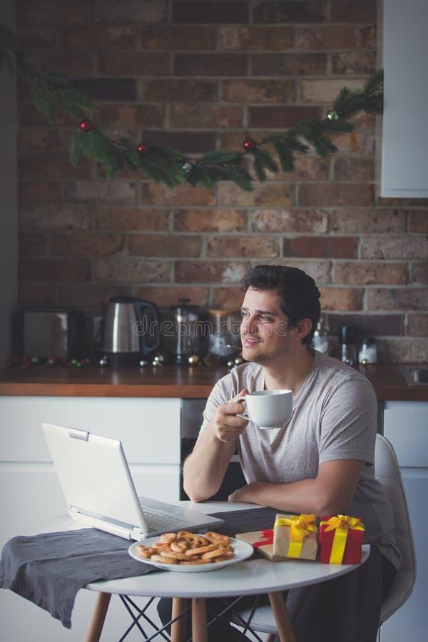 Человек с чашкой чаю или кофе и портативным компьютером стоковые изображения